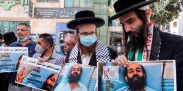 Palestinian protesters and members of an anti-Zionist Jewish movement hold signs in solidarity with Palestinian prisoner Maher al-Akhras.