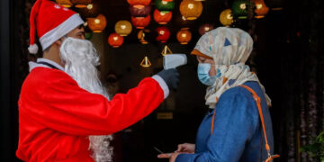 A Palestinian employee dressed as Santa Claus takes a customer's temperature at a cafeteria in Gaza City.
